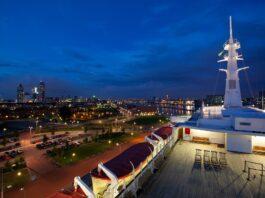 Uitzicht op de skyline van Rotterdam bij avond vanaf het dek van de SS Rotterdam
